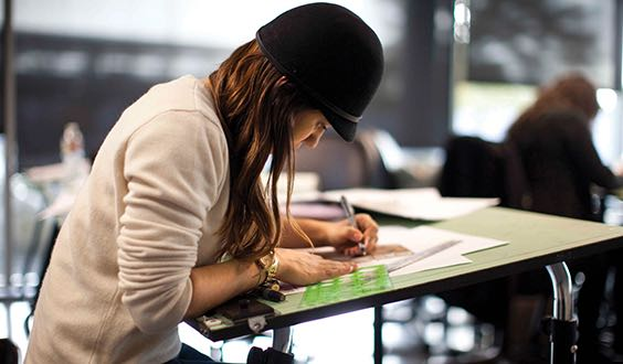Female student drawing on drafting table