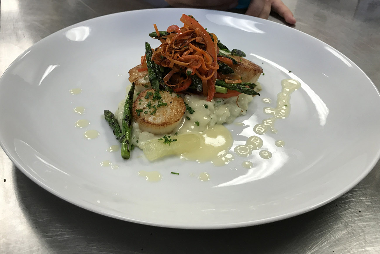 Seared Scallops with a Lemon and Herb Rissoto and creamy Lemon Buerr Blanc Sauce, grilled asparagus and julienned carrots and red bell pepper, garnished with chopped parsley and lemon segments