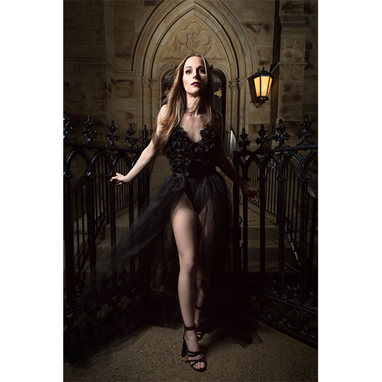 Fashion model posses at gothic style church black dress
