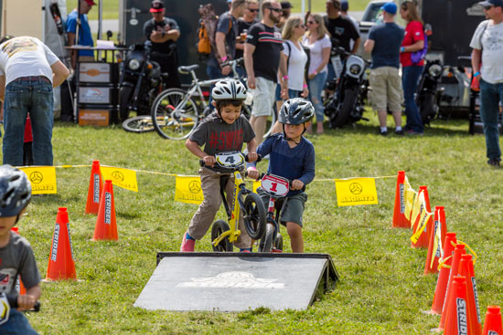 Kids practice stunts on balance bikes and ramps