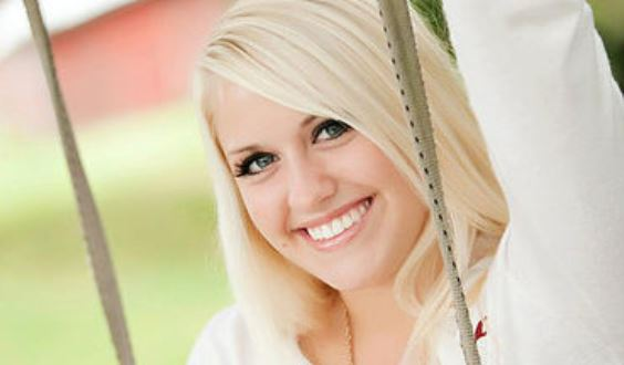 Headshot of Olivia Cline Graphic Design student on swing with blond hair