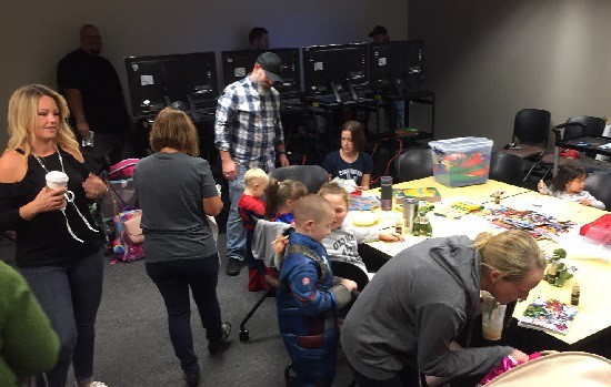 Families and superheroes enjoy activities in the waiting room prior to their photoshoot.