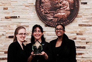 Three women hold up trophy for competition teams