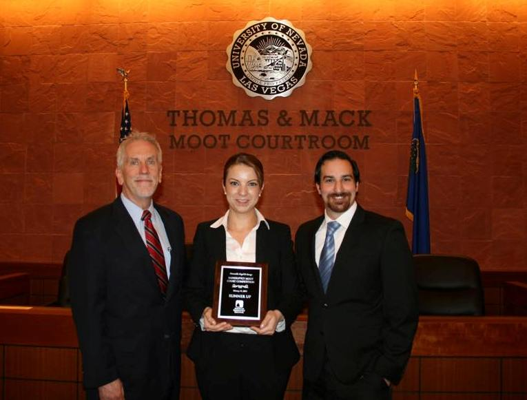 Three people hold trophy by Moot Court
